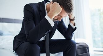 Executivo sentado na cama de hotel, com as mãos na cabeça. Ao lado dele, uma mala de viagem.