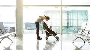 Mulher com carrinho de bebê em aeroporto