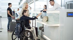 Passageira idosa acompanha passageira em cadeira de rodas na área de check-in de aeroporto
