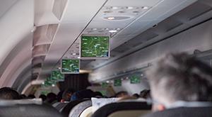 Imagem interna de avião com passageiros observando as telas de informação