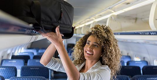 Passageira acomoda sua bagagem de mão no compartimento do avião