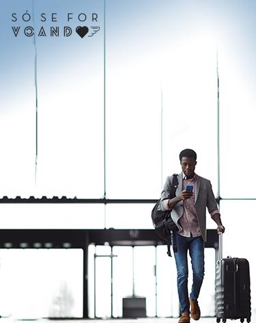 Passageiro caminhando no aeroporto carregando uma mala de mão, uma mochila e mexendo no celular